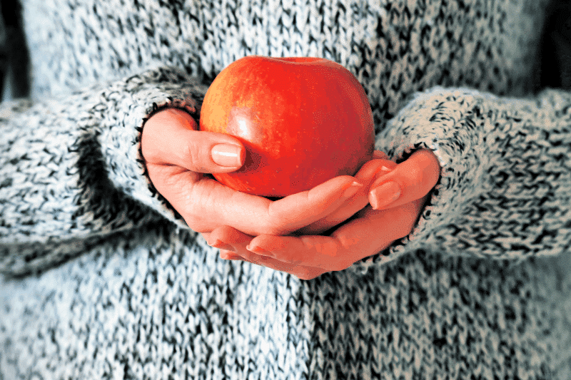Woman holding apple symbolizing virtuous cycle to get back on track