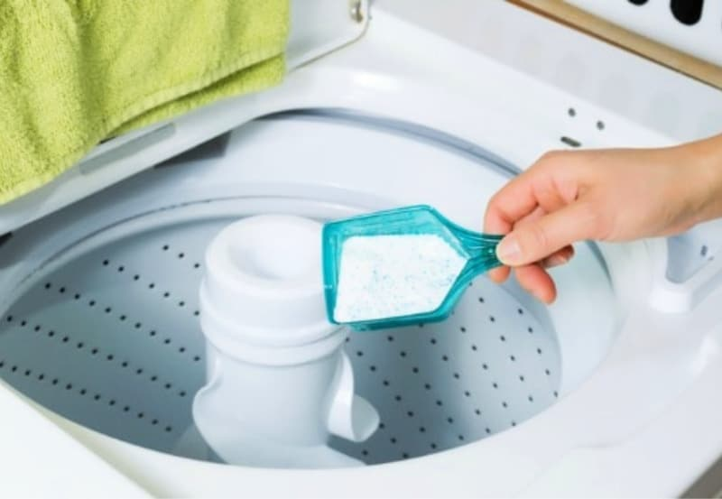 Woman pours powdered detergent into clean top loading washing machine