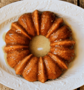 Banana Bundt Cake with Caramel Sauce on a white serving platter against a wood background