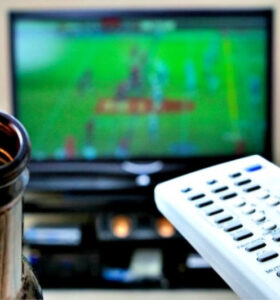 Closeup of brown beer bottle and TV remote with football game on TV in background