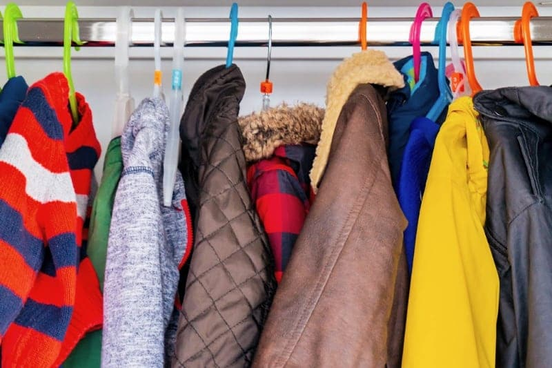 Adult and childrens winter coats and hoodies hanging from plastic hangers in a coat closet that needs organizing