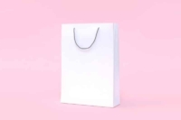 White paper shopping bag against a pastel pink background