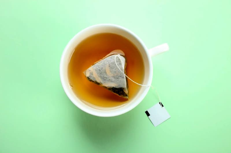 Tea and tea bag in white cup against green background