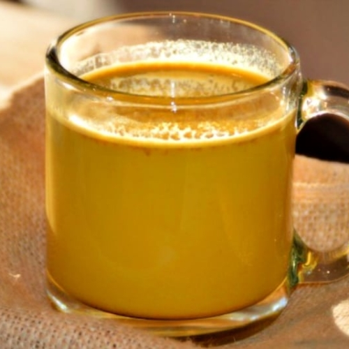 Golden Turmeric Milk Latte Recipe in a cup sitting on top of a canvas cloth