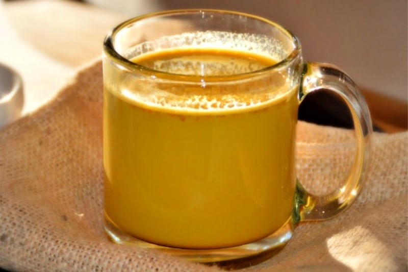 A cup of homemade Golden Turmeric Milk Latte recipe sitting on a canvas napkin