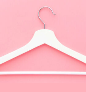 An empty white clothing hanger laid flat on a pink background