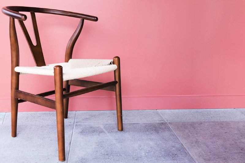 Wood chair with curved back and woven seat on a cement floor with a pink wall behind it
