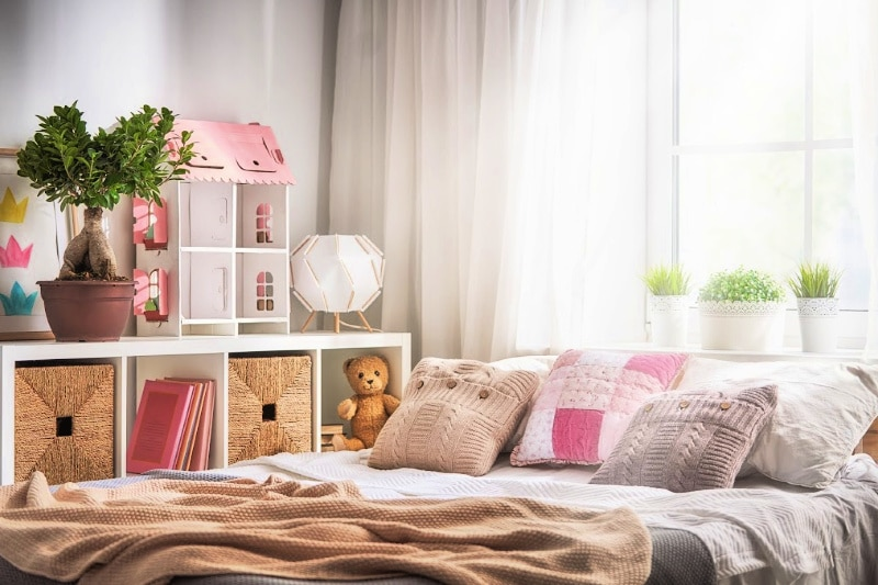 Clean and organized kids bedroom with pink and white accents on bed and dollhouse