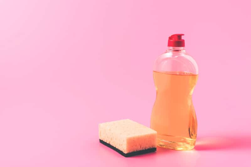 Bottle of liquid dish soap and kitchen sponge on pink background