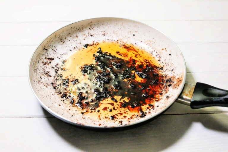 Overhead of enameled skillet with greasy burned-on food