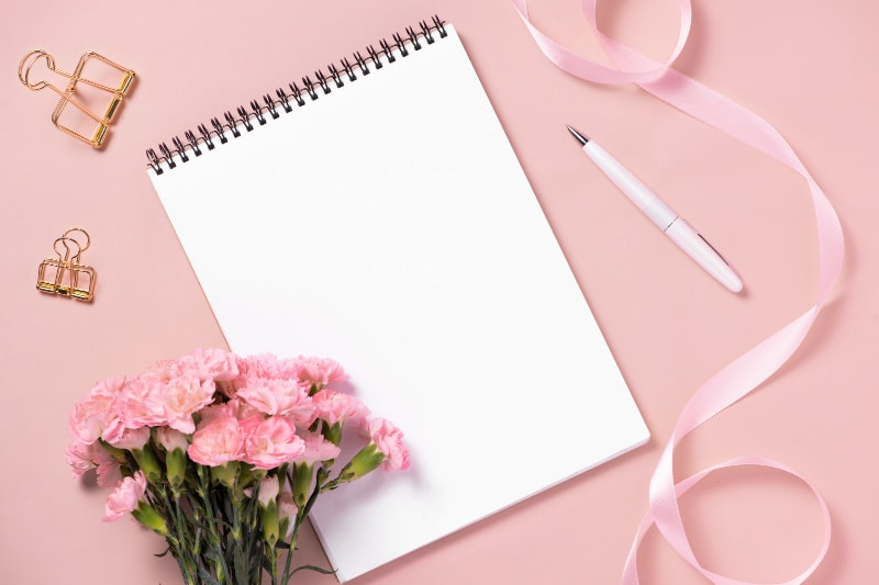 Blank notebook and office supplies on a pink background
