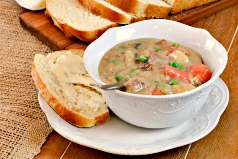 Irish Lamb Stew recipe in a white bowl on a side plate with a slice of buttered Irish potato bread