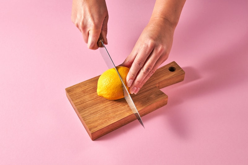 Uses for lemons - overhead shot of two hands holding a lemon and knife over a wood cuttingboard