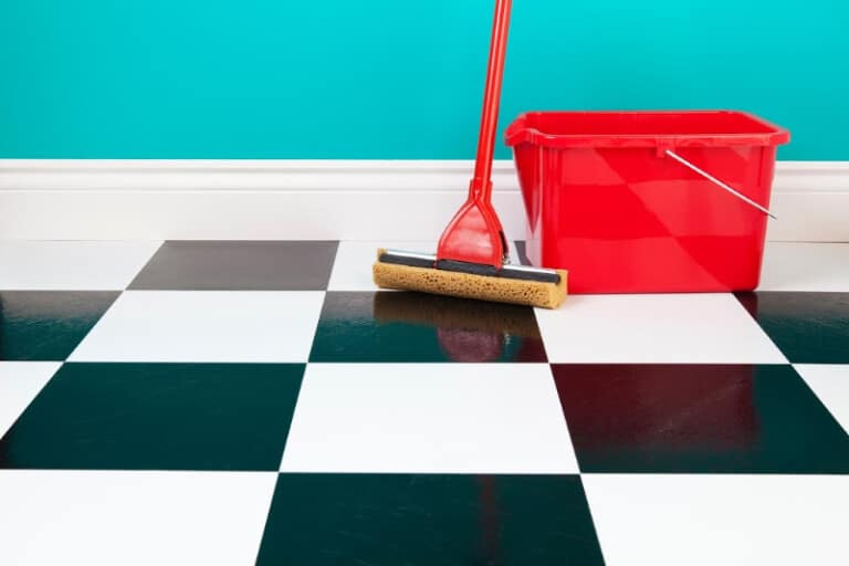 Homemade floor cleaner in a red bucket next to a mop on top of a black and white checkered tile floor