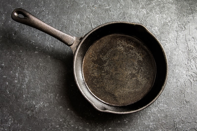 Dirty cast iron pan on a rough gray background
