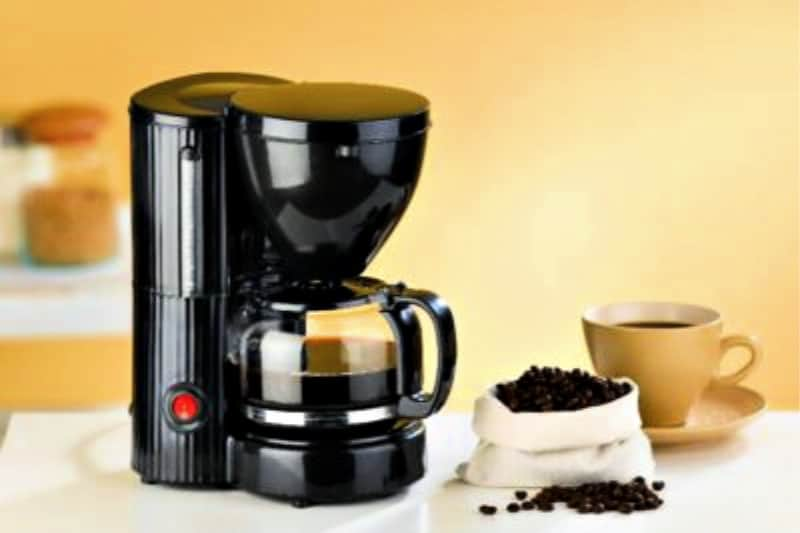 Coffee maker and open bag of beans near yellow cup and saucer on a kitchen counter