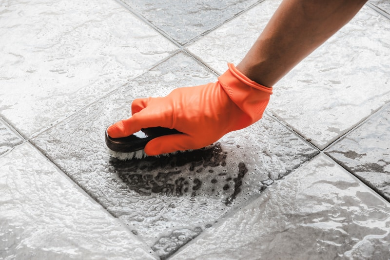 Hand in orange glove holding scrub brush to clean bathroom grout on floor