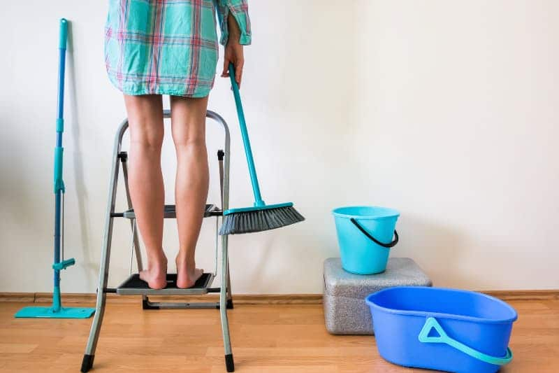 Woman on step stool holding broom with cleaning supplies on the floor next to her