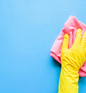Hand in rubber glove using a pink microfiber cloth on a blue background