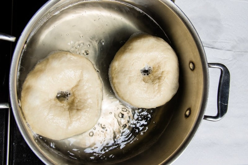 Overhead shot of bagels being boiled in a pot on the stove