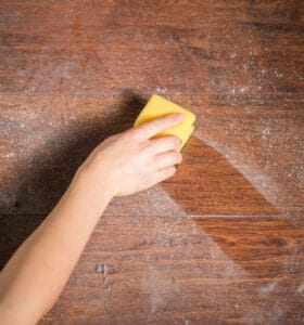 Hand holding sponge to wipe a clean path through dust on a wood table