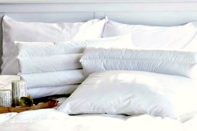 Clean and fluffy white pillows piled on a bed next to a tray