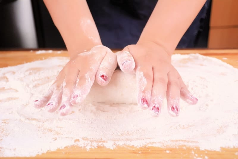Closeup of a woman using her hands to knead dough on a floured surface