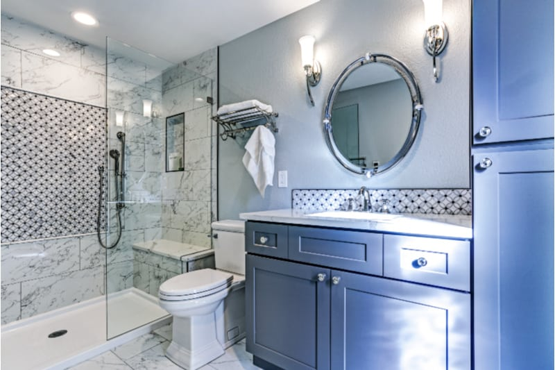 Modern bathroom with blue cupboards and marble shower enclosure