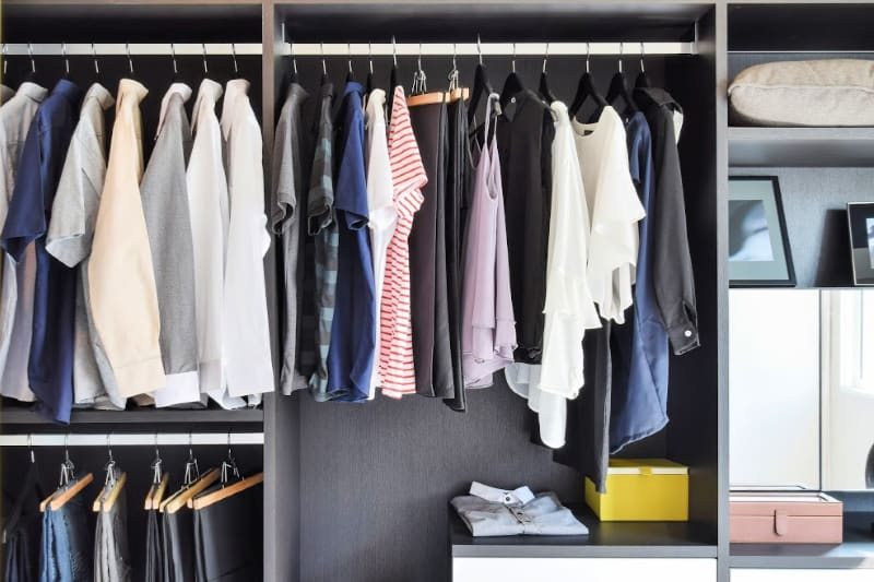 Modern closet with man and woman's clothes hanging from rods