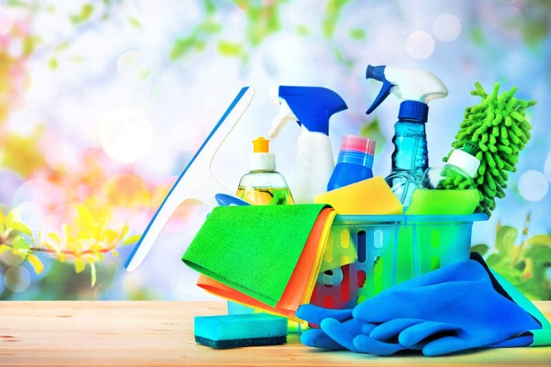 Cleaning products and tools in a bucket on wood counter with floral background