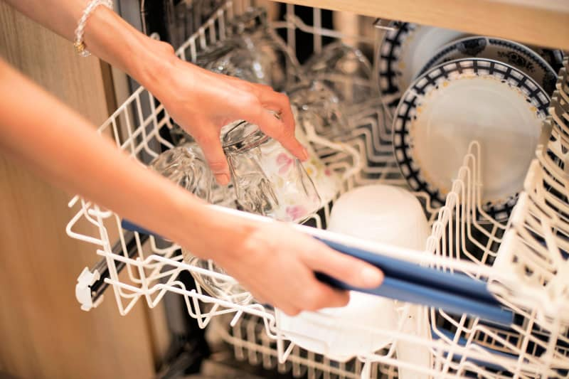Closeup of woman loading dishwasher