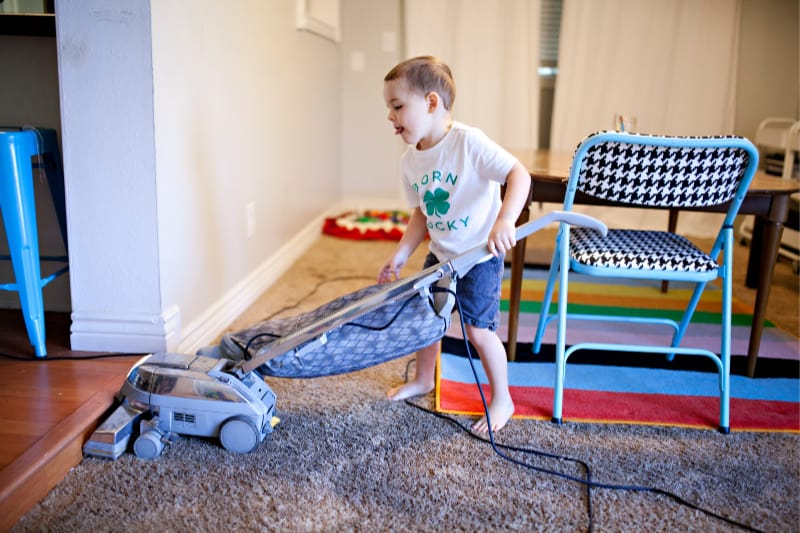Young kid helping to clean house by vacuuming floor