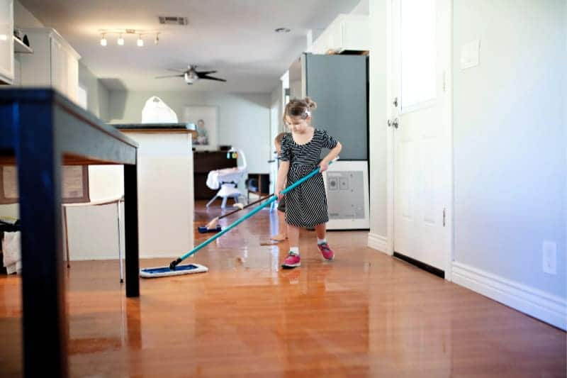 Young kids helping clean house by using dust mops on wood floor