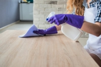 Woman wearing rubber gloves and a microfiber cloth while holding a spray bottle of homemade all-purpose cleaner as she wipes a wood countertop
