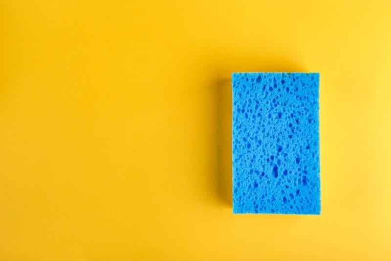 Blue kitchen sponge on yellow background