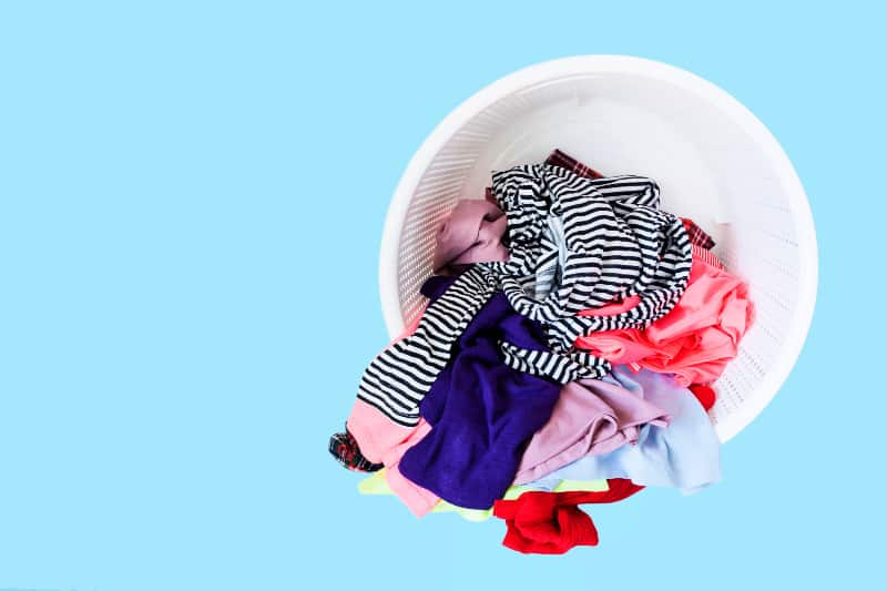 How to Disinfect Laundry: Jumble of clothing in a round plastic laundry hamper against a blue background