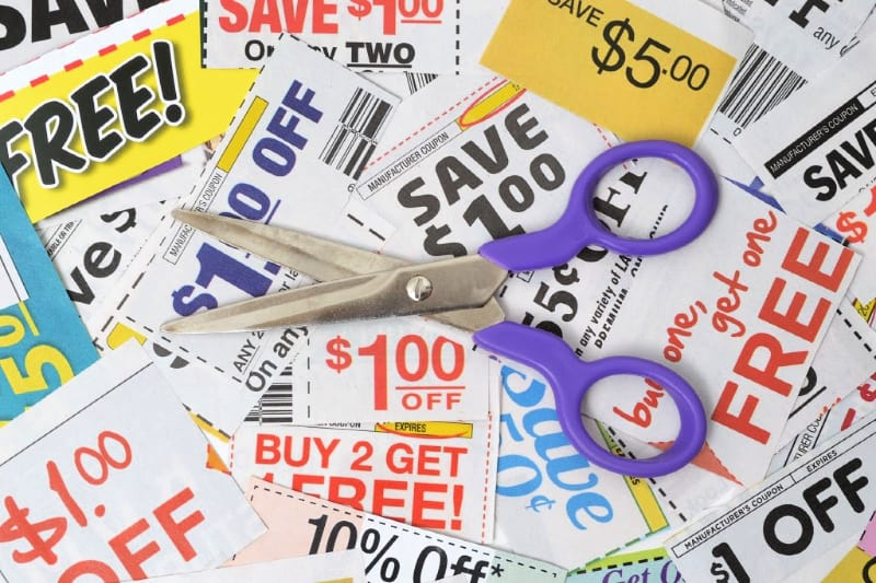 Overhead shot of assorted coupons and open scissors