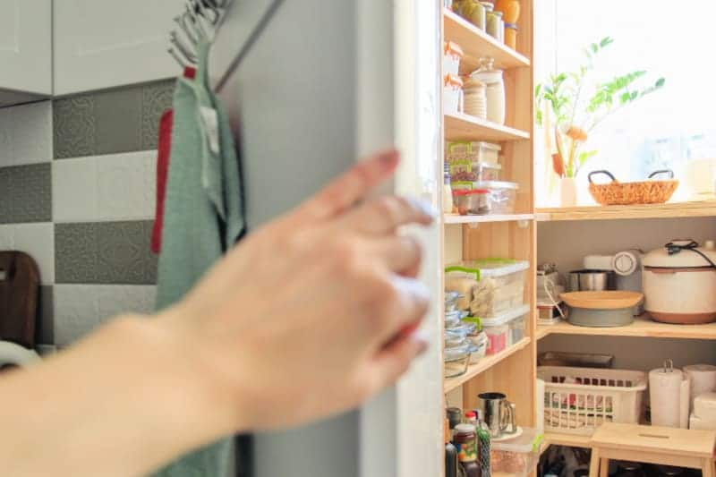 Hand opening door to view of stocked pantry