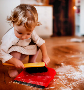 Toddler girl sweeping spilled flour from floor by hand