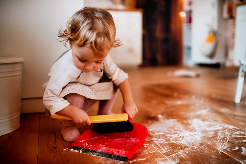 Toddler girl in a dress using a dust pan and hand broom to clean spilled flour on floor