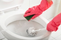 Woman scrubbing toilet with sponge and brush