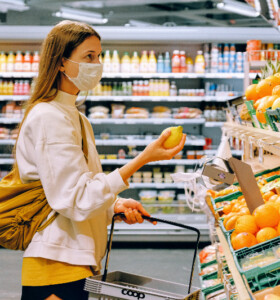 Woman wearing cloth face covering while shopping for groceries