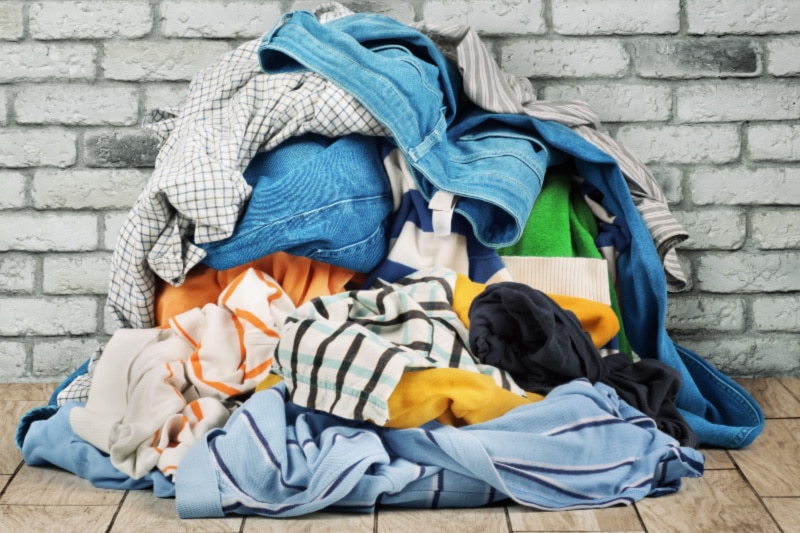 Pile of unsorted dirty laundry on a wood floor