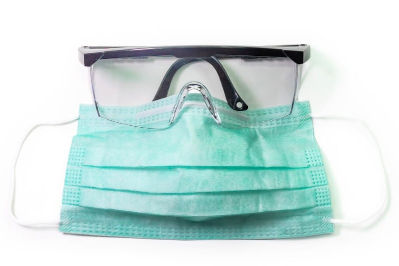 Eye glasses positioned over top edge of surgical mask and metal strip bent to keep glasses from fogging
