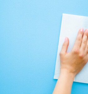 Woman's hand wiping flat surface with paper towel