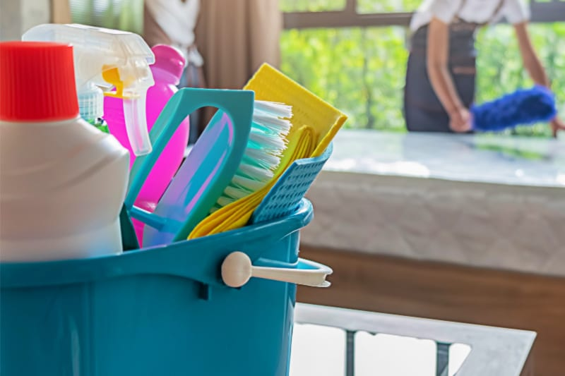 Bucket of cleaning supplies on counter with woman dusting in the background
