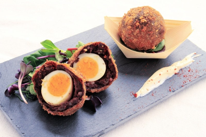 Traditional Scotch Egg sliced open and served on platter with microgreens