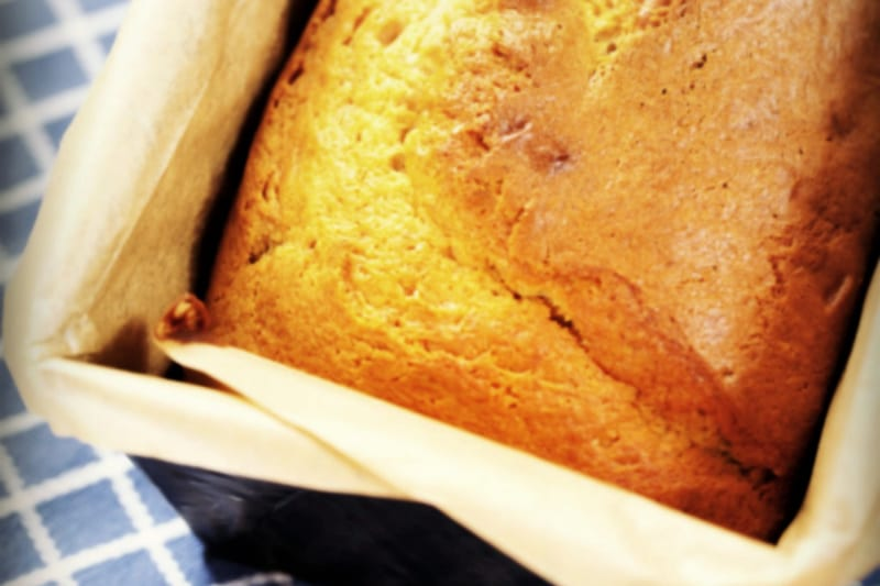 Freshly baked loaf of banana bread without sugar in a parchment-lined pan