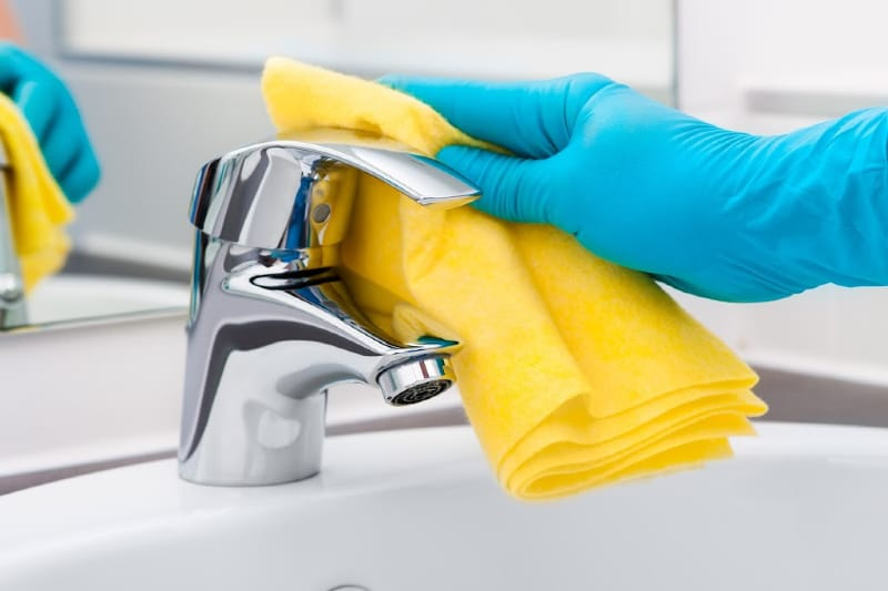 Hand in rubber glove using microfiber cloth and homemade soft scrub to clean bathroom sink tap