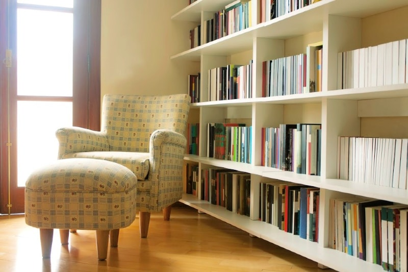Comfortable chair and ottoman next to home library bookshelves